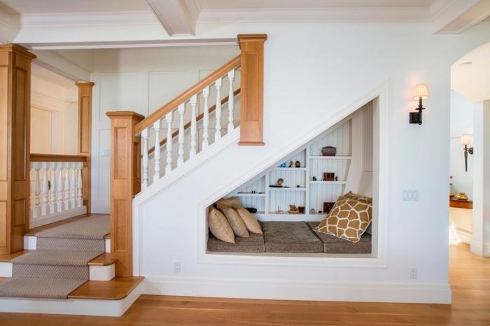 etagere sous pente en bois peint en blanc avec banc et coussins décoratifs pour un coin de lecture sous l'escalier