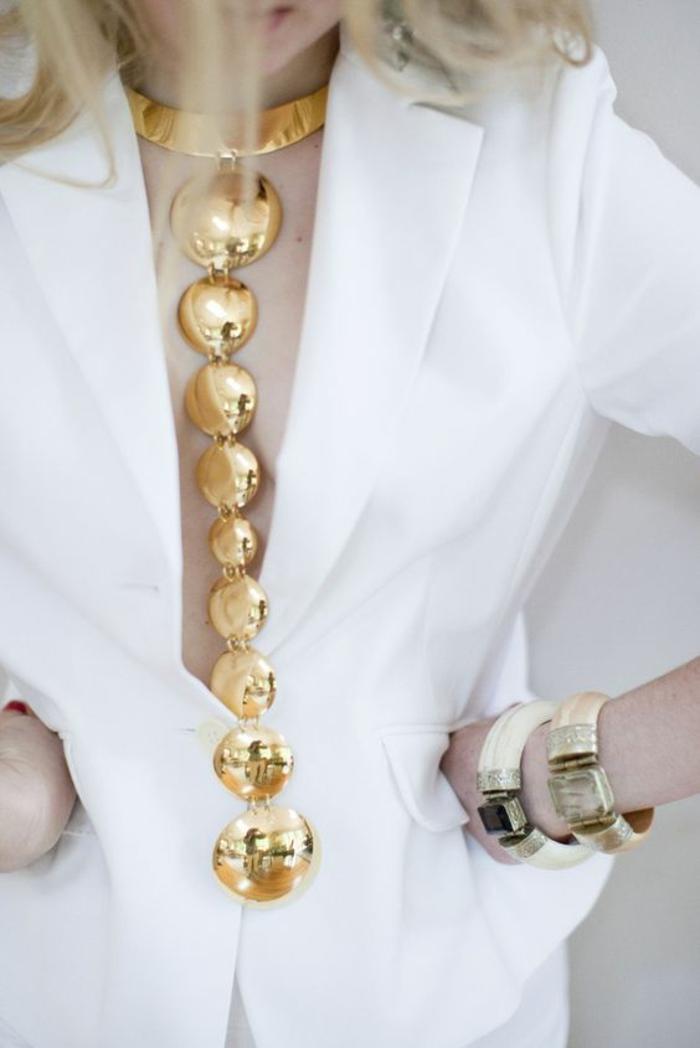 bijou extravagant et long avec des boules en métal couleur or, soirée chic détail choc, bijou porté sur une veste blanche classique