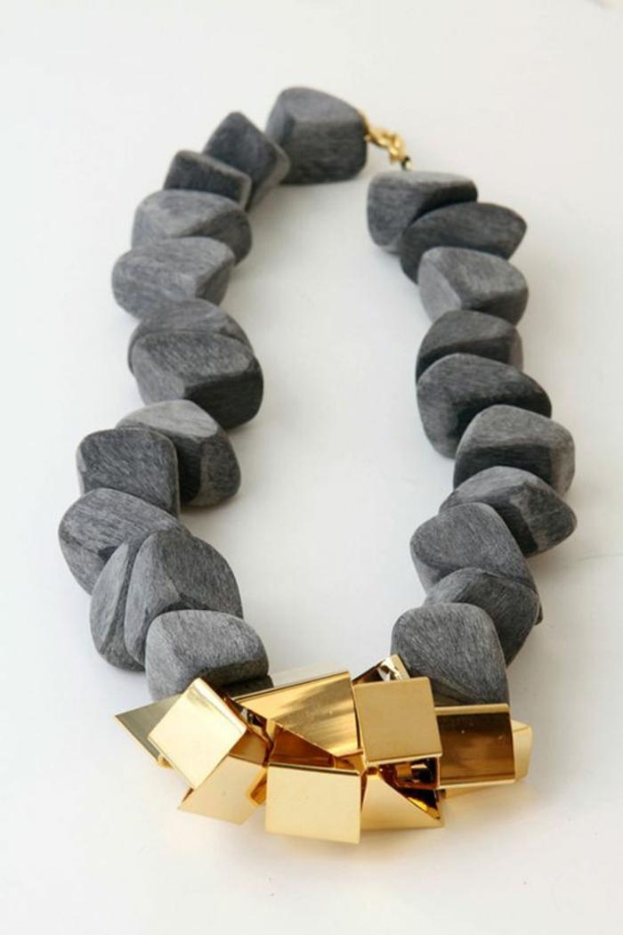 bijou accessoire avec des pierres grises de fleuve et des cubes et triangles en métal doré, soirée chic et choc, style élégant et provocant