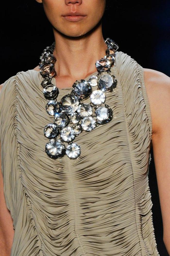 top sans manches avec des effets drapés en couleur beige sable, collier grande taille avec des grands pierres blanches et rondes Swarovski, haut chic bas choc