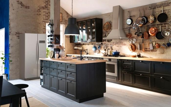 déco de style loft industriel avec murs en briques rouges et blanches, cuisine avec ilot central en noir et bois
