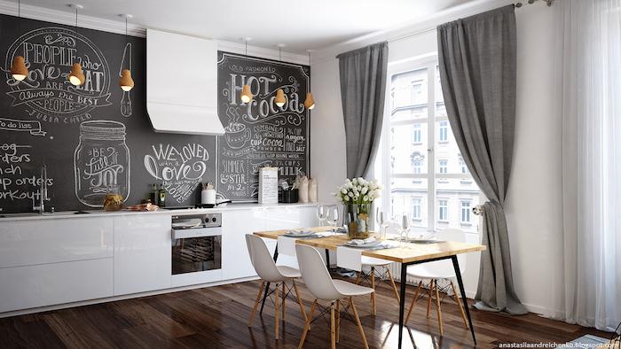 modele de cuisine avec meuble bas blanc laqué et mur en tableau noir craie, dessins artistiques à la craie, parquet marron foncé, table en bois et metal et chaises scandinaves