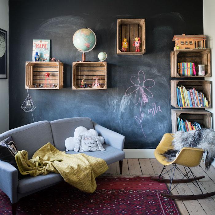 idée pour aménager un salon cosy avec un mur de fond en peinture ardoise, tapis rouge oriental, canapé gris, chaise a bascule jaune, cagettes bois deco