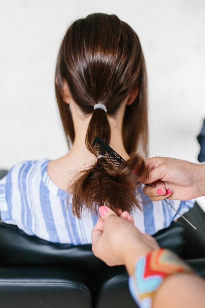 idée pour une coiffure cheveux mi long avec chignon bas de cou et deux tresses entrelacées fixées dessus