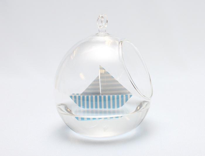 décoration de baby shower sur thème marin, mini-bateau origami qui flotte dans une boule transparente
