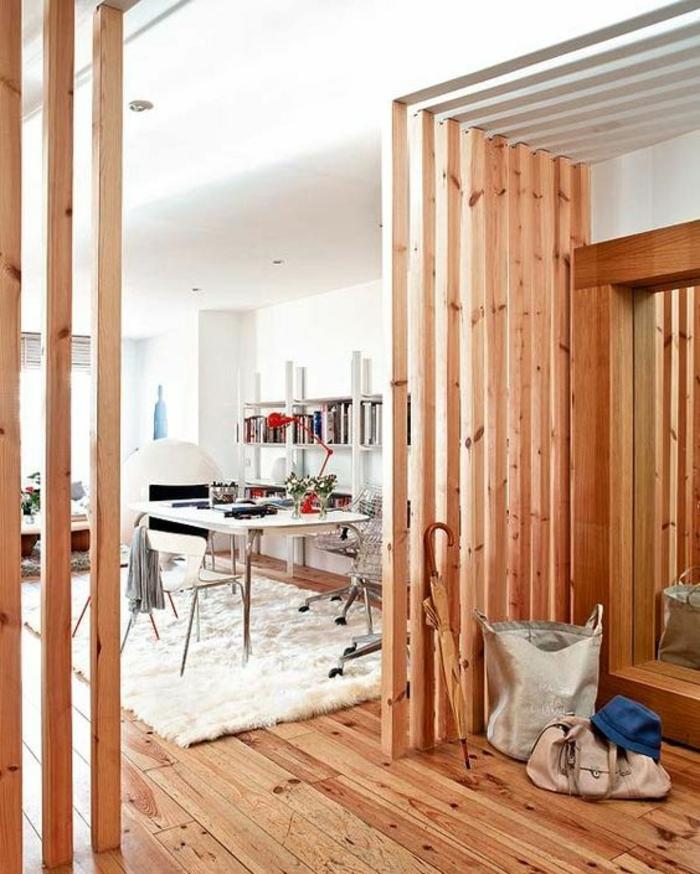 ambiance boisée en nuances cerise, cloison separation, pièce avec tapis rectangulaire en blanc, table rectangulaire blanche, sol en planches en bois