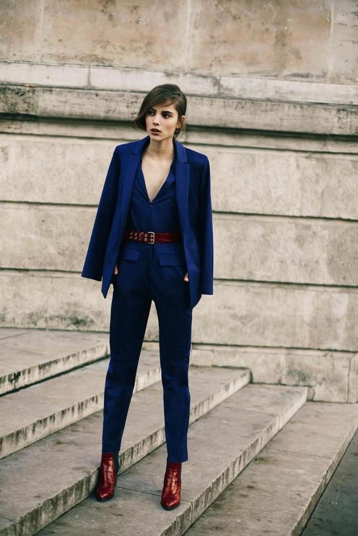 tenue chic avec costume femme de trois pièces en bleu marine ajustée à la taille avec une ceinture de la même couleur que les bottines