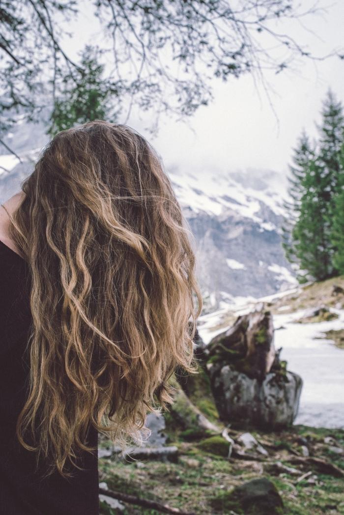 couleur de cheveux, coiffure naturelle aux cheveux longs et bouclés de nuance châtain foncé avec mèches éclaircies
