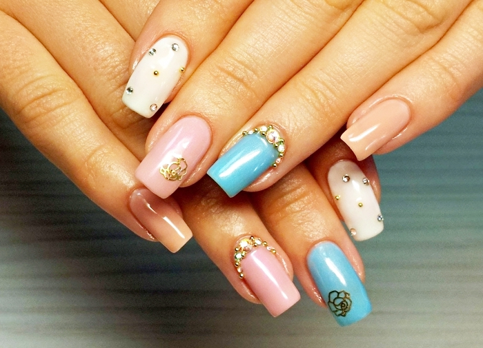extensions ongles gel en couleurs rose et bleu avec décoration en stresse doré et petit sticker floral