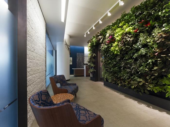mur vert dans le couloir, décoration avec des plantes vivantes, tapis crème, grandes chaises