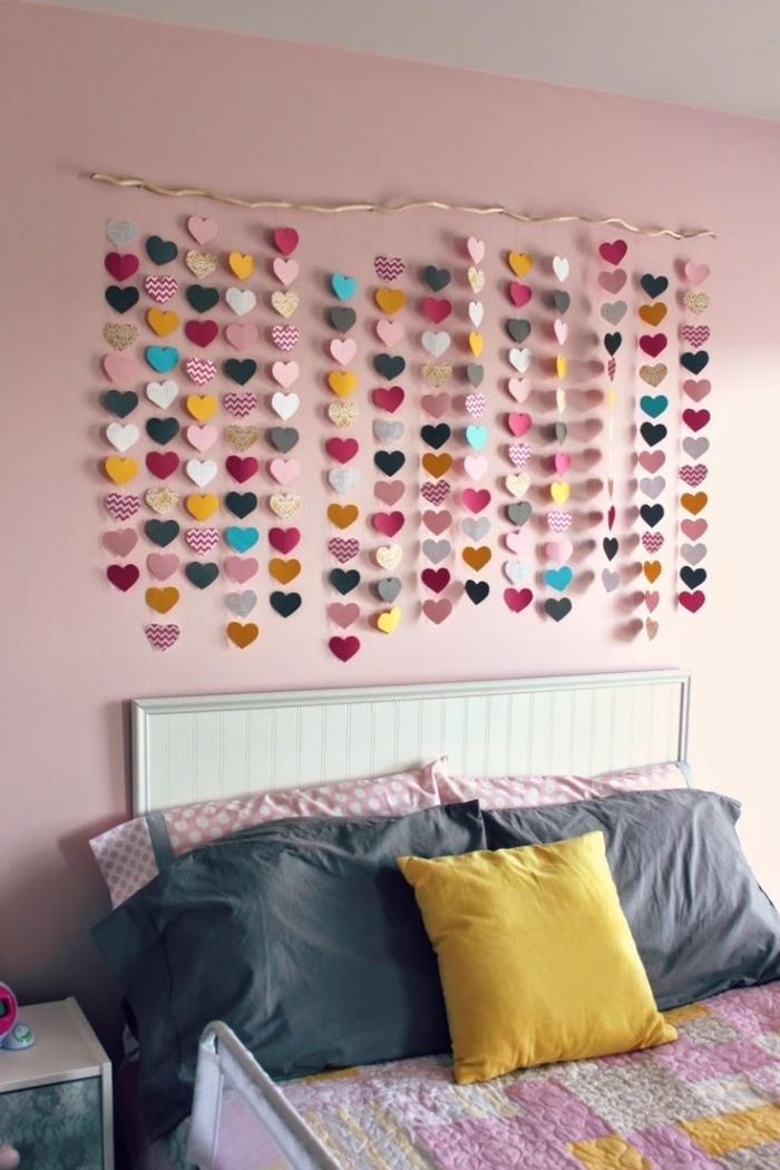 décoration murale avec petits coeurs de papier coloré accroché sur le mur peint en rose pale