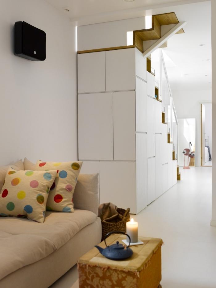 espace ouverte dans le salon vers le couloir aux murs et plancher blanc avec rangement sous l'escalier