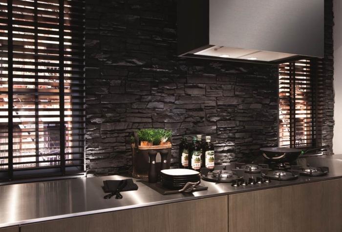 revêtement mural en pierres dans une cuisine aménagée avec armoires de bois et comptoir à design métallique