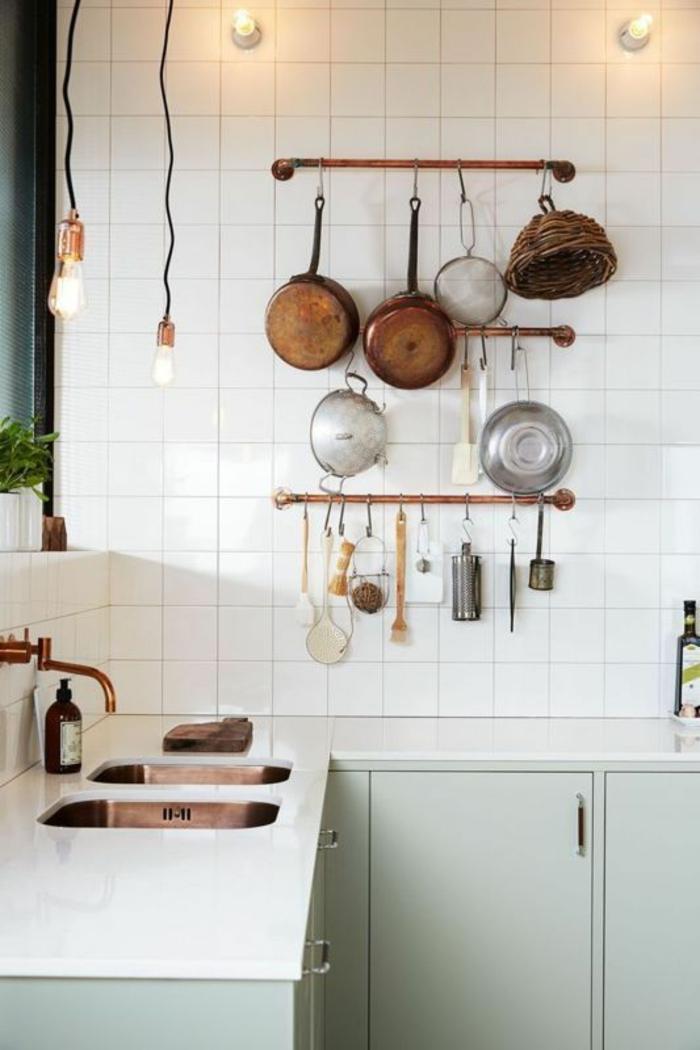 cuisine petit espace, ustensiles de cuisine suspendus au mur, carrelages blancs classiques aux murs, des ampoules nues suspendues sur des fils longs