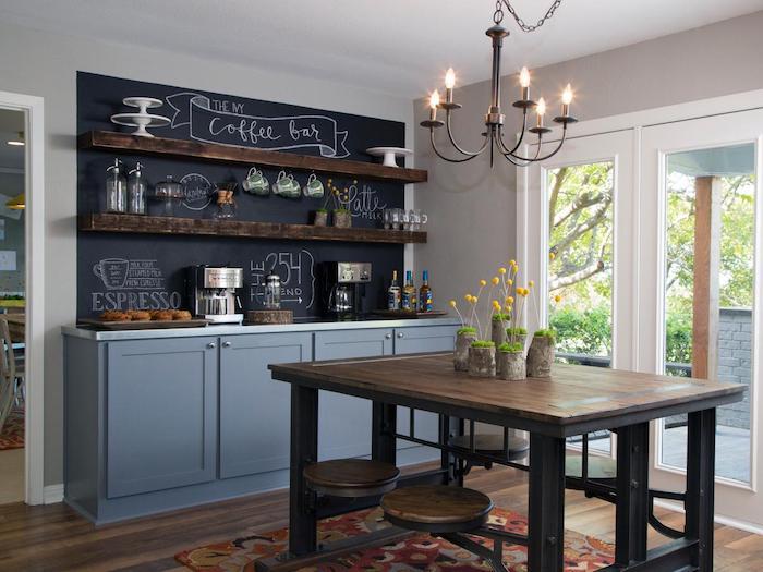 modele de cuisine campagne chic avec meuble bas gris, credence cuisine en tableau noir craie, etageres en bois brut ouvertes, table avec tabourets en bois et metal
