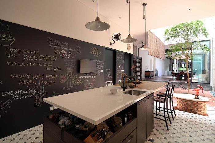 cuisine aménagée avec ilot central doté de plan de travail blanc, sol en carreaux de ciment et mur en ardoise murale en lettres colorées