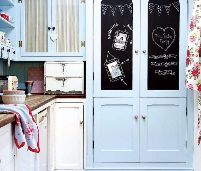 idée de cuisine campagne chic en bleu pastel, armoire bleu décoré de peinture ardoise magnétique et dessins à la craie, plan de travail bois marron, mobilier vintage