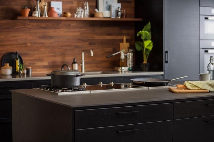 idée déco de cuisine moderne avec meubles noirs et crédence en bois marron foncé, cuisine noir mat
