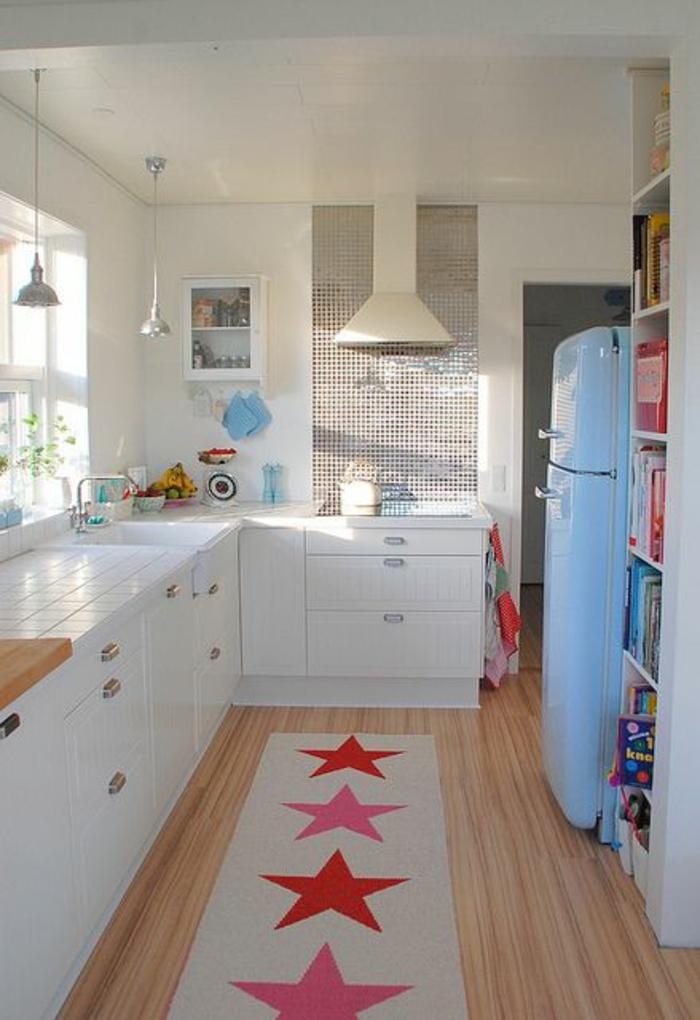 petite cuisine équipée, cuisine en longueur, meubles blancs, tapis long rectangulaire en blanc avec des étoiles rouges et roses, frigo en bleu pastel