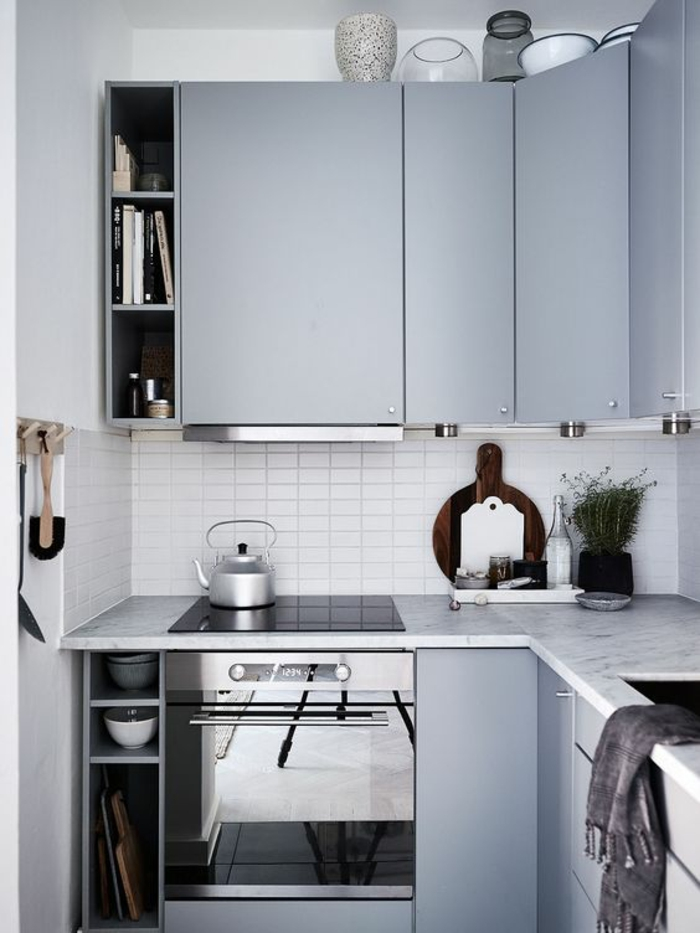 petite cuisine équipée, meubles angulaires en couleur bleu pastel, crédence en petites briques blanches, cuisine petit espace, plan de travail des meubles en surface aux effets marbre
