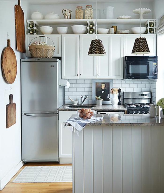 petite cuisine équipée, meubles de cuisine, meubles classiques blancs, haut frigo en couleur argent, étagères blanches au-dessus des meubles de cuisine, luminaires en canne tressée, parquet jaune
