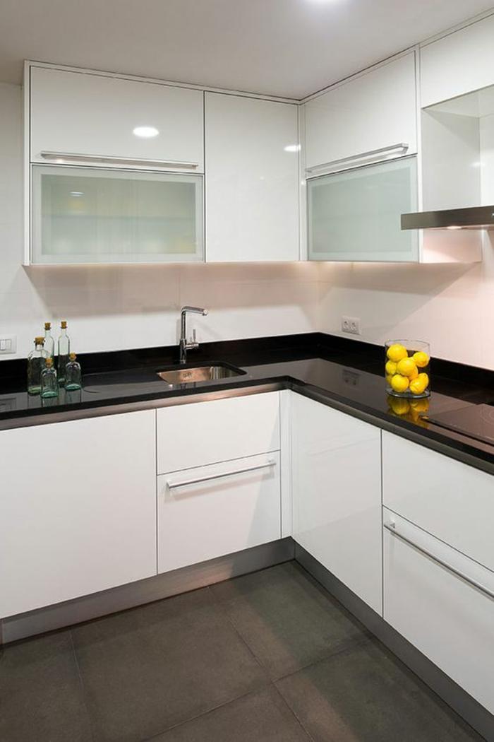 petite cuisine équipée, meubles angulaires blancs avec plan de travail noir brillant, sol avec carrelage en couleur taupe, plafond blanc, meubles avec des poignées longues en métal couleur argent
