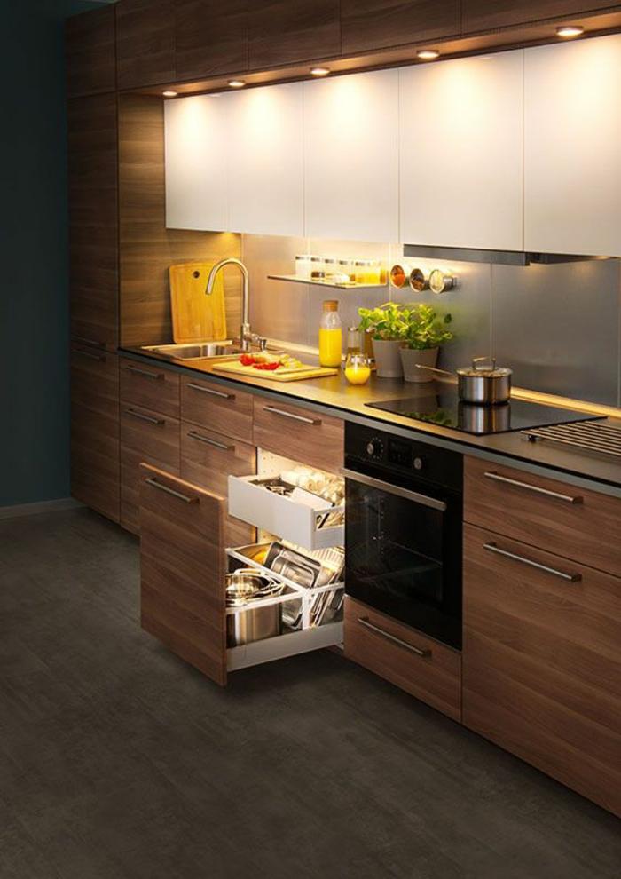 petite cuisine équipée, meubles avec surface en revetement imitation bois facile a entretenir, petits luminaires ronds au-dessus du plan de travail et des fourneaux, sol avec parquet PVC en nuances grisâtres