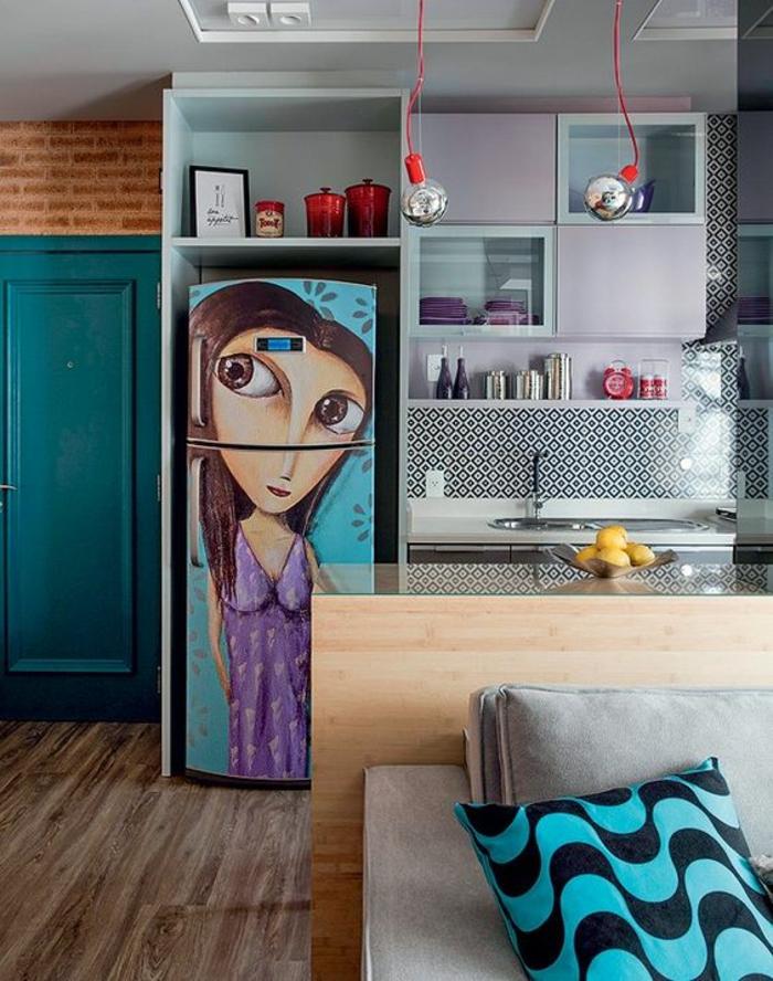 cuisine en longueur, frigo haut en couleur bleu turquoise avec image de fillette aux grands yeux, ouverture de l'espace cuisine sur le salon, porte en couleur bleu canard, deux corps luminaires suspendu avec fil rouge vif, canapé en premier plan avec des grands coussins , parquet en gris et marron