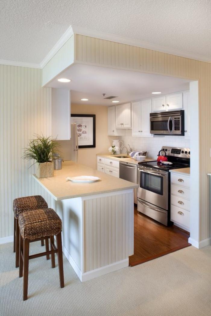 amenagement petite cuisine, box en forme de cube avec plan de bar, meubles classiques blancs, deux tabourets de bar avec des pieds longs en bois clair et partie en tissu marron et jaune