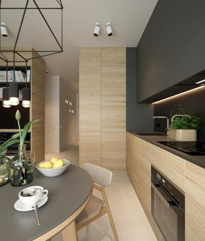 cuisine en longueur, meubles de cuisine, meubles et murs en beige clair, revetement imitation bois, luminaires en forme de tubes blancs, table ronde avec plan gris et des pieds en beige clair, sol avec carrelage en beige