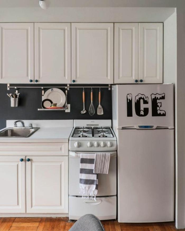amenagement petite cuisine, haut frigo blanc avec inscription GEL en noir et blanc, parquet en jaune, meubles blancs massifs, crédence en couleur gris anthracite, ustensiles suspendus au-dessus du lavabo et au-dessus des fourneaux