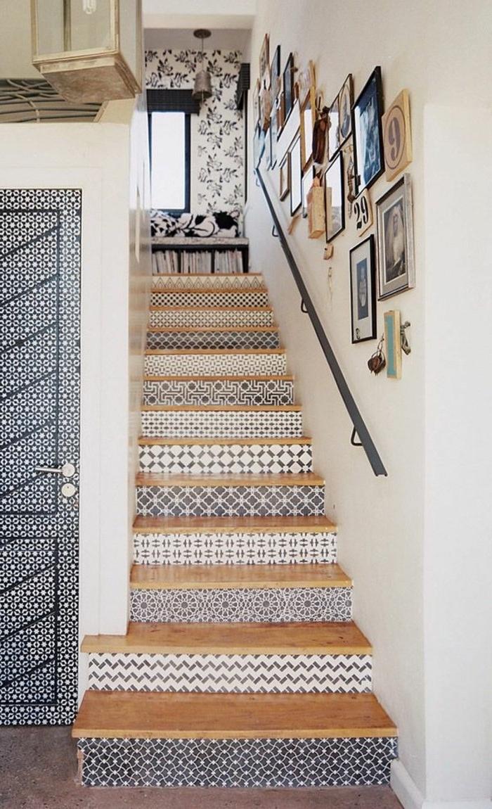 des contre-marches agrémentées de stickers escalier imitant des carreaux de ciment à motifs bleu variés qui reprend le style de la porte et du pan de mur en papier peint