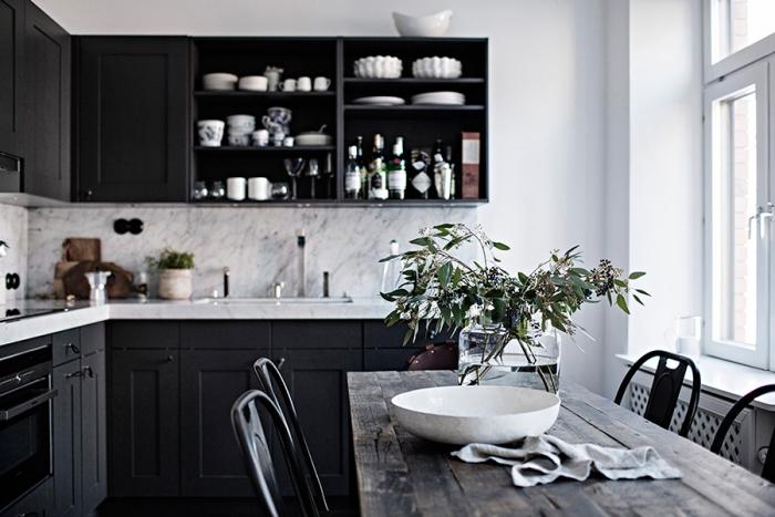 intérieur moderne et traditionnel avec armoires noires et crédence à design marbre gris et blanc dans une cuisine aménagée