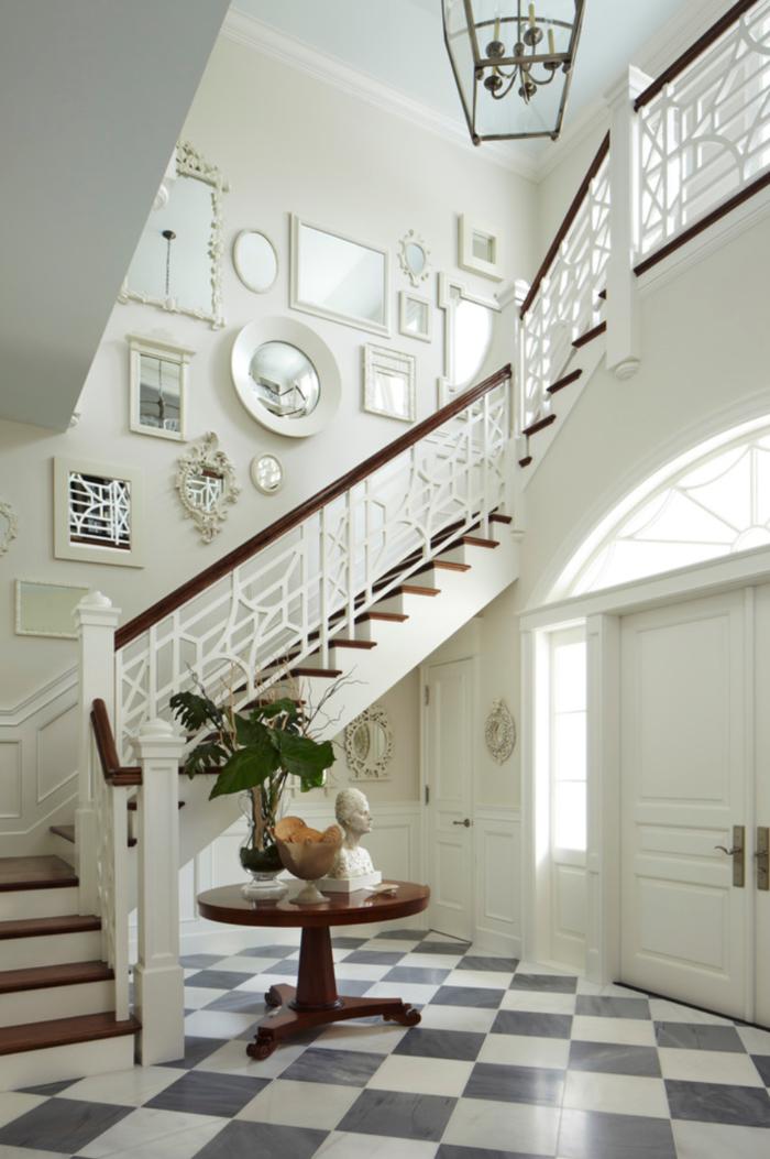 hall d'entrée élégante en blanc au carrelage damier avec en escalier repeint en blanc et un mur décoré de miroirs