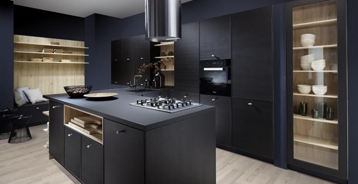 coin de repos avec murs en bois clair et banc noir décoré de coussins en nuances pastel, cuisine bistrot noire