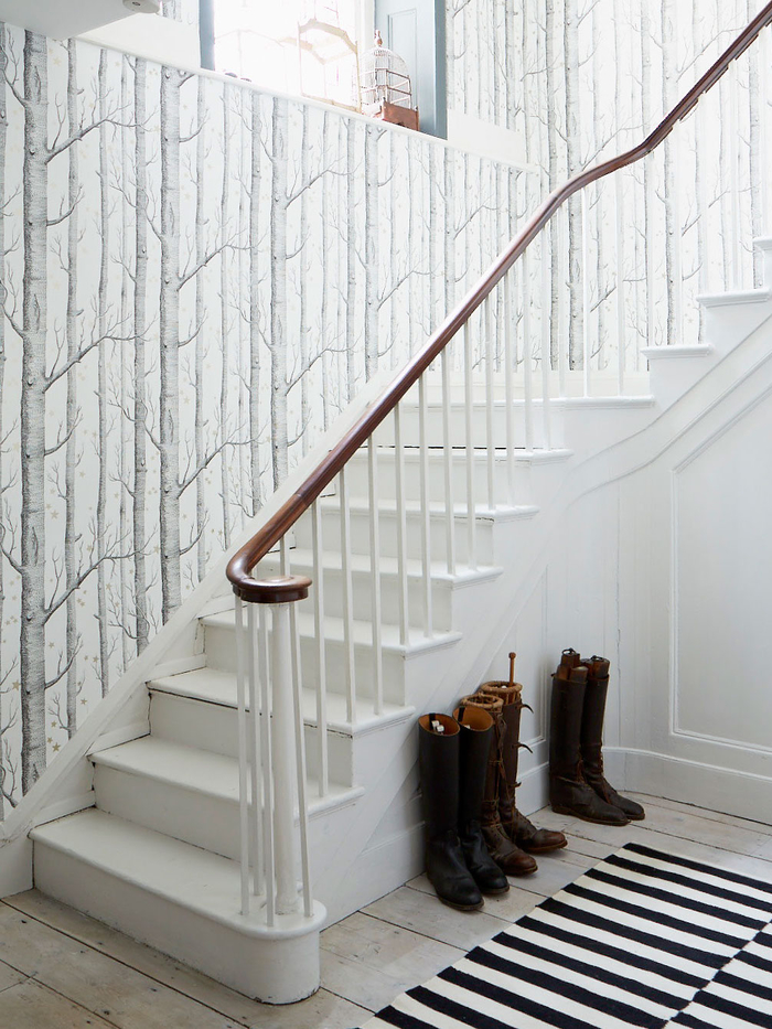déco montée d'escalier de style nordique épuré avec un papier peint à motif arbre qui se fond avec l'escalier et le parquet blanc