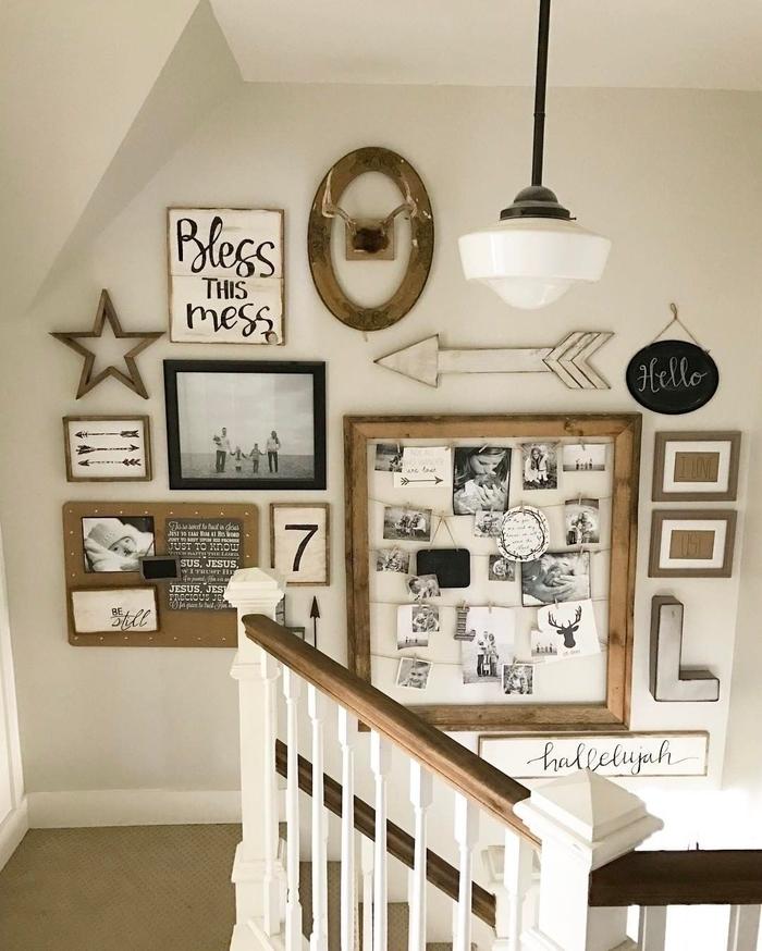 une deco montee escalier avec un pêle-mêle de cadres photos et d'enseignes en bois