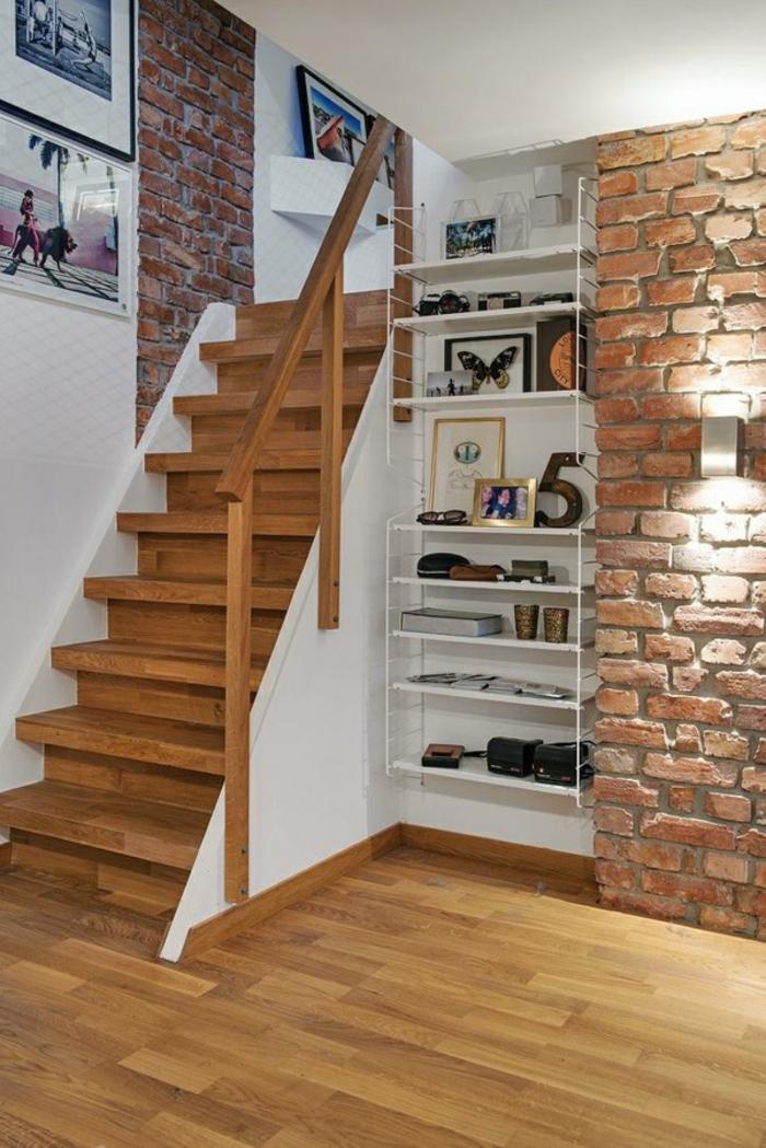 petit escalier en bois qui se fond dans la déco de la chambre, décoré d'un pan de mur en briques et des cadres photos