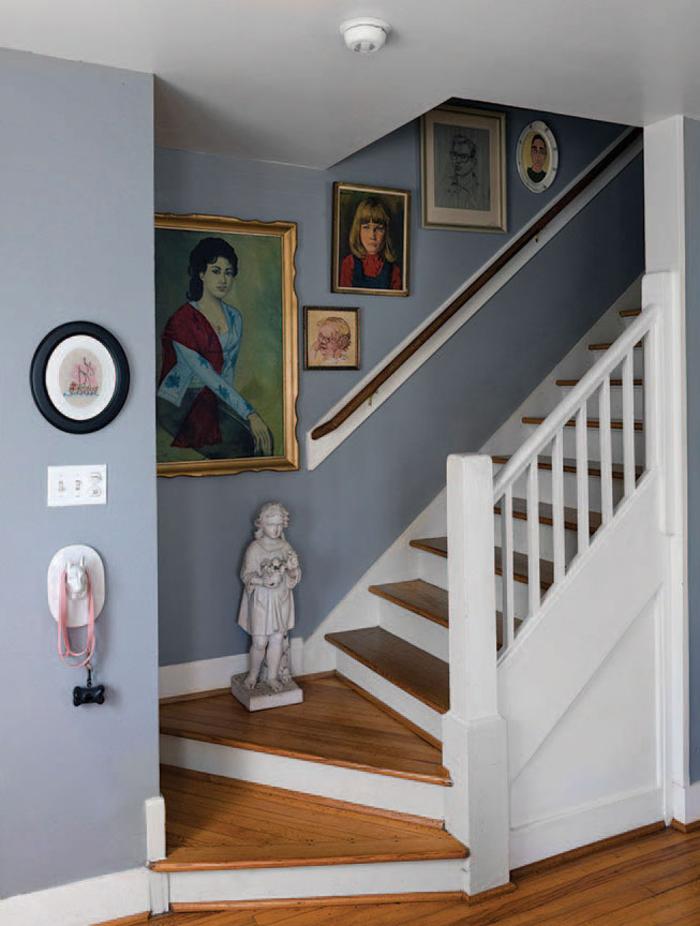 petit escalier repeint en nuance douce du bleu-gris en harmonie avec les contremarches et la balustrade blanches, décorée d'une galerie murale vintage