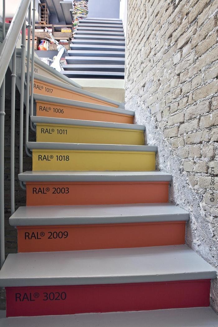 projet original pour un escalier repeint aux couleurs pantone en contraste avec le mur en brique à effet brut