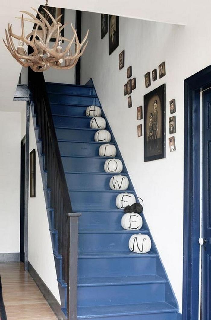 deco montee escalier pour la fête d'halloween avec des citrouilles repeintes à chaque marche, escalier peint en bleu en contraste avec les murs blancs