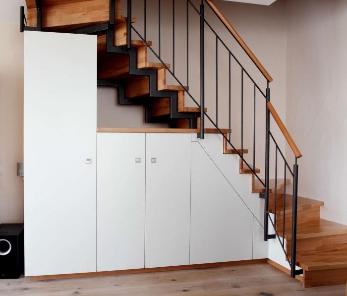 tendance intérieur en bois et noir matte avec rangement sous escalier aux armoires blanches