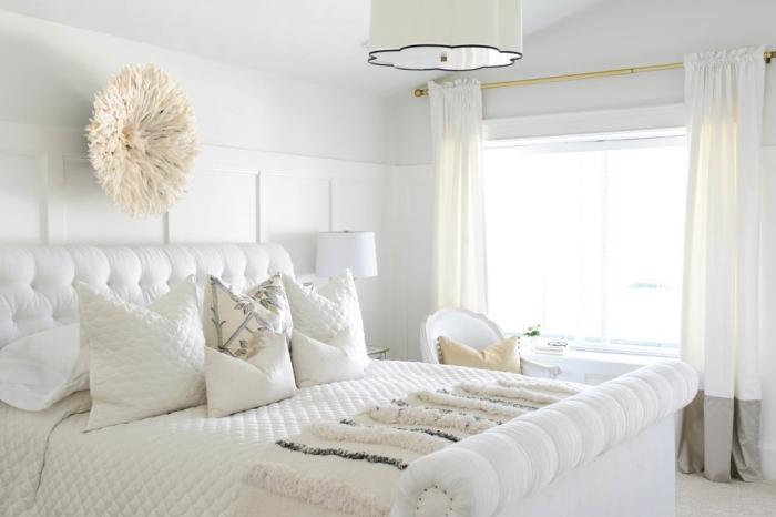 meuble chambre blanche à design cocooning avec déco murale à imitation pouf en faux fur beige et coussins