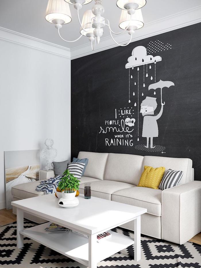 exemple de déco salon avec mur de fond en peinture craie, canapé blanc cassé, table basse blanche et tapis noir et blanc, lustre élégant