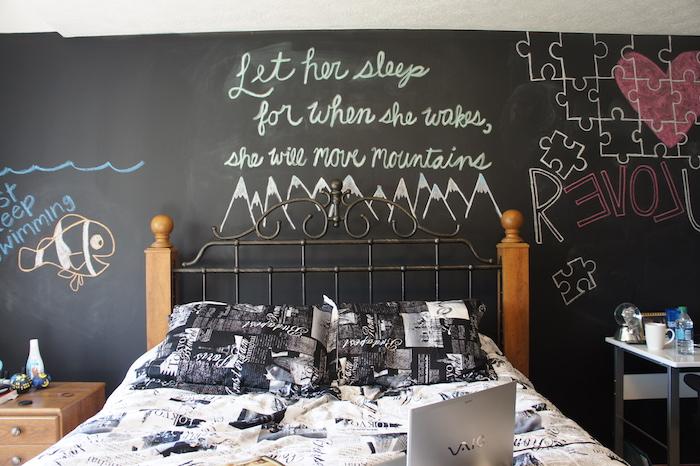 mur en peinture tableau noir craie, lit en bois et metal, linge de lit noir et blanc, dessins et citations sur un mur