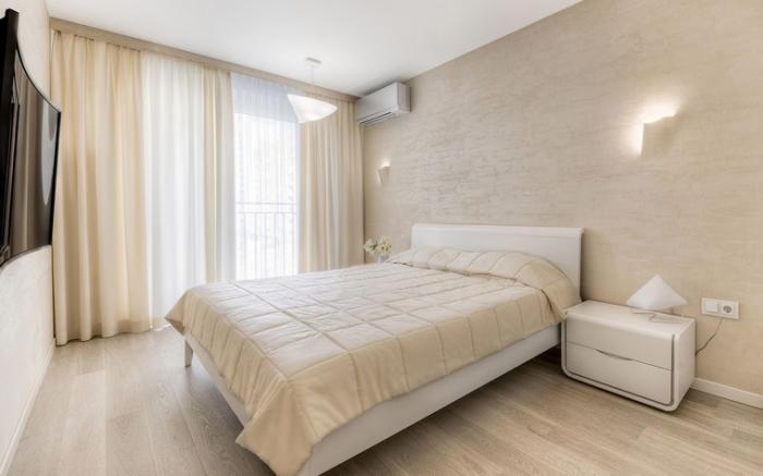 aménagement stylé à design minimaliste avec meuble chambre moderne de couleur blanc, revêtement murale en papier peint à imitation bois