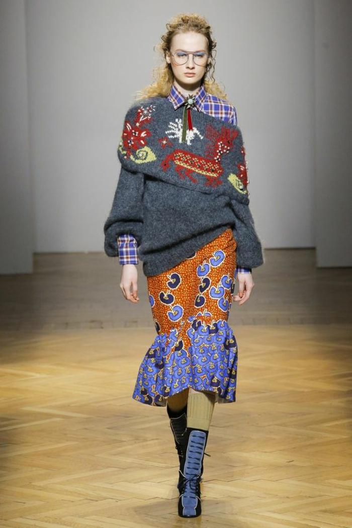 la designer Stella Jean avec un modèle de pagne wax, vetement africain, jupe avec des motifs ethniques, portée avec un gros pull gris pastel, avec le col orné de motifs lamas en rouge