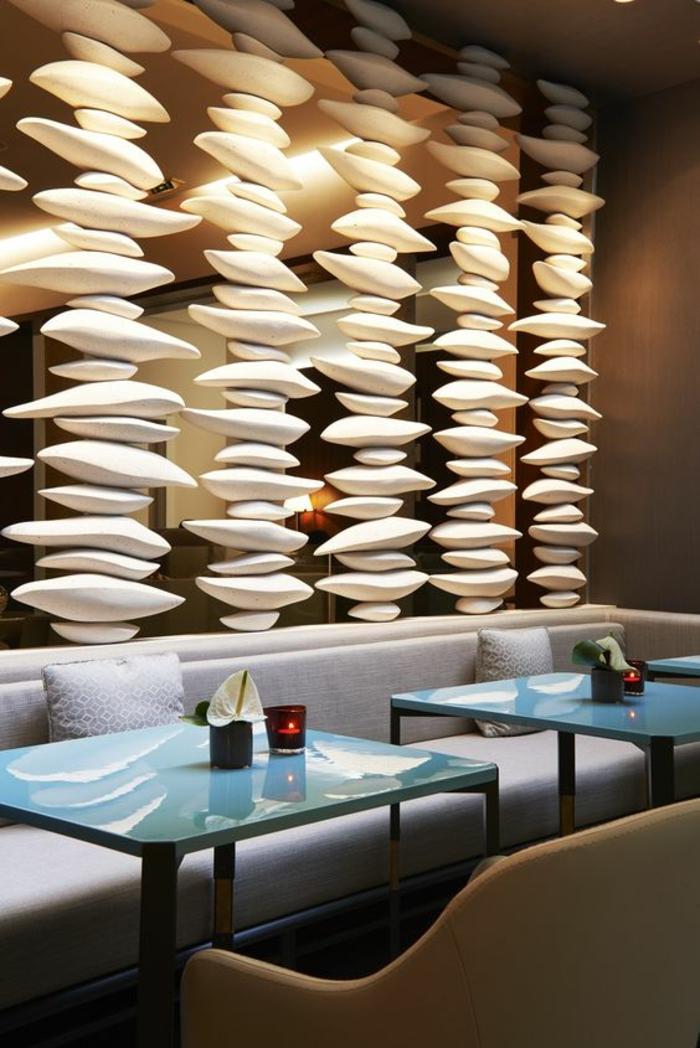 panneau de séparation, rideau de séparation, avec des pierres blanches ovales pour une ambiance zen, canapé blanc avec des tables carrées en bleu