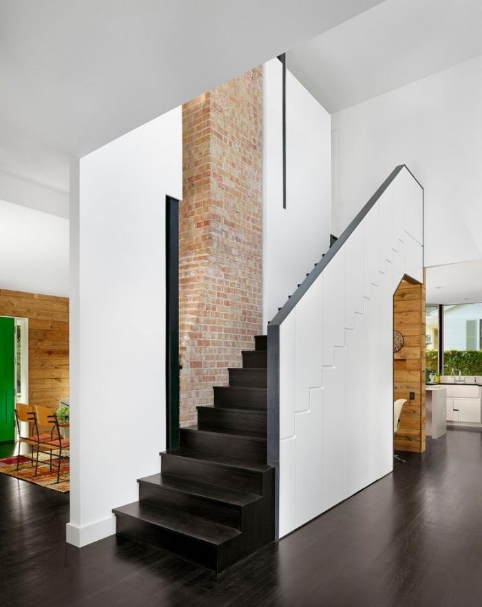 déco moderne en blanc et noir avec mur de briques rouges, meubles design avec rangement sous escalier coulissant