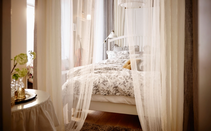 ambiance romantique dans la chambre à coucher avec voiles beige et lit de cadre bois blanc, déco du plancher en bois avec tapis moelleux en marron